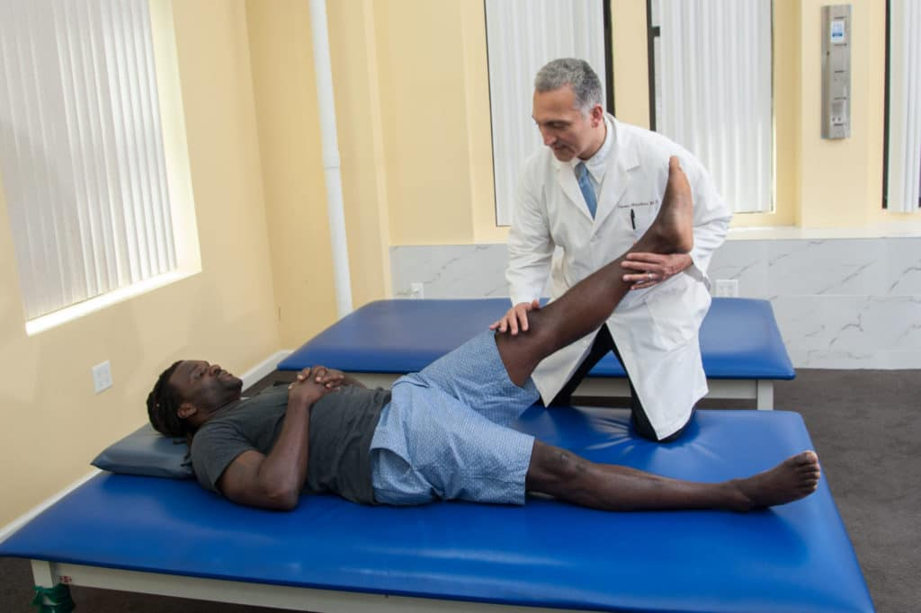 the doctor gives physical therapy adjustment to nfl patient